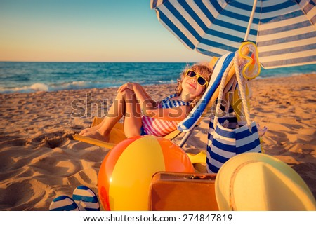 Happy child sitting on the sunbed. Funny kid at the beach. Summer vacation concept - stock photo