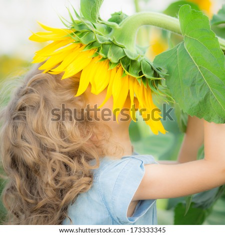 Happy child smelling beautiful sunflower outdoors in spring field - stock photo