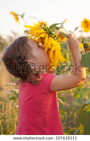 Happy child smelling big sunflower. Unity with nature.