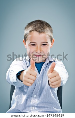 Happy Child Smiling with Thumbs Up Over a Grey Background