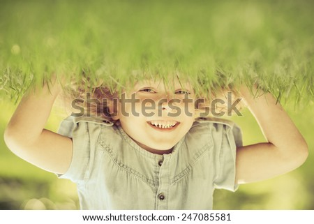 Happy child standing upside down on green grass. Laughing kid having fun in spring park. Healthy lifestyle concept - stock photo
