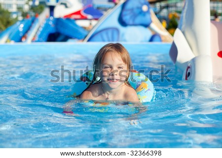Happy child swimming in pool with rubber ring - stock photo