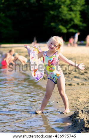 Happy child swimming in the lake. Healthy smiling toddler girl relaxing in the water using inflatable ring. Active summer vacation concept. - stock photo
