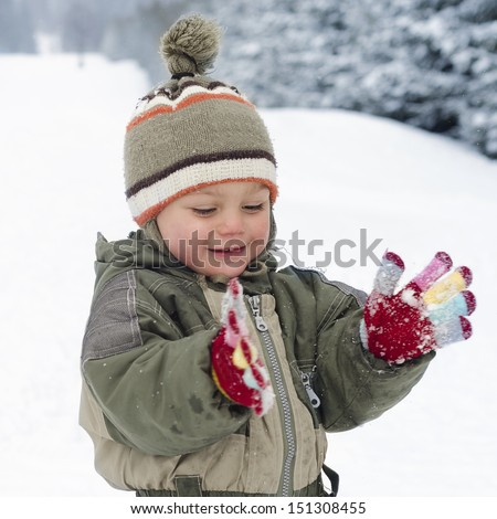 Happy child toddler, boy or girl, playing in fresh snow in winter.  - stock photo