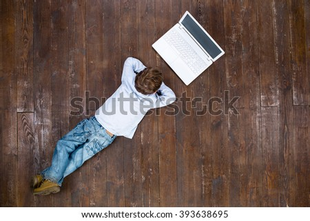 Happy child. Top view creative photo of little boy on vintage brown wooden floor. Boy using laptop - stock photo