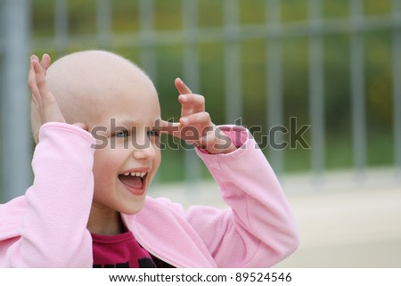happy child who lost her hair due to chemotherapy to cure cancer - stock photo