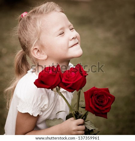 happy child with a bouquet of red roses - stock photo