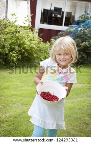 Happy child with a bowl of freshly picked berries - stock photo