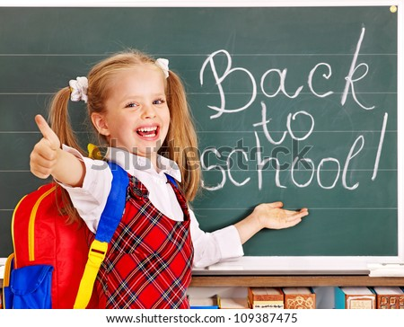 Happy child with backpack holding book. Isolated. - stock photo