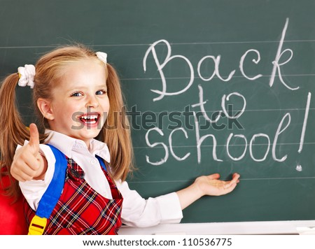 Happy child with backpack writting on blackboard. - stock photo