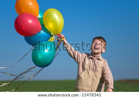 Happy child with balloons running on the spring field - stock photo