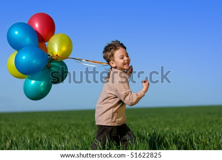 Happy child with balloons running on the spring field