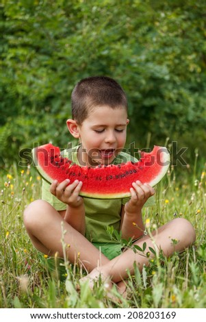 Happy child with big red slice of watermelon  - stock photo