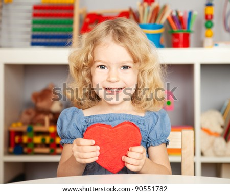 Happy child with handmade paper red heart in class. School concept - stock photo