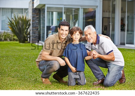 Happy child with his father and grandfather in a garden in front of a house