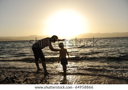 Happy child with his father at sea together. Sunset - stock photo