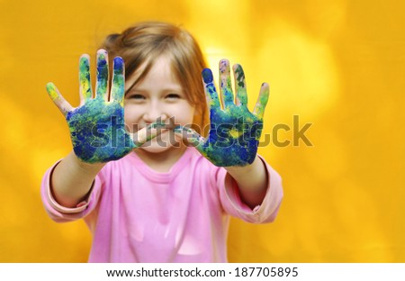 Happy child with painted hands.  Painted hands. - stock photo