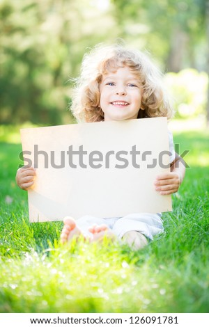 Happy child with paper blank sitting on green grass in spring park - stock photo
