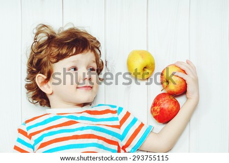 Happy child with red apples on light wooden floor. Top view. - stock photo