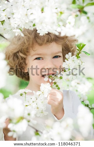 Happy child with spring flower. Ecology concept - stock photo