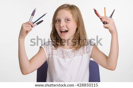 Happy child with stationery in her hands. Young girl demonstrates everything needed for lessons in school. The set of pens and pencils. Smiling kid with opened mouth. - stock photo