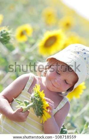 happy child with sunflower in summer field - stock photo