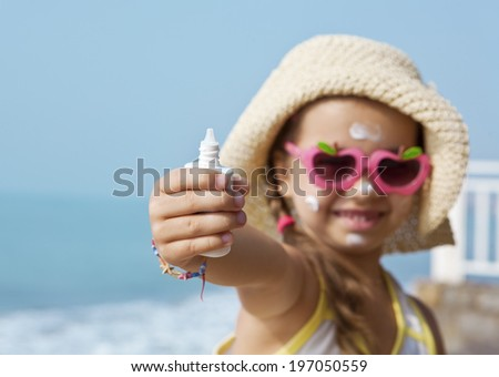 Happy child with sunscreen in hand against the sea. The focus of the tube. - stock photo