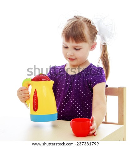 Happy childhood, adolescence, the development of the family concept.Little girl sitting at the table pouring from a plastic tea kettle. Isolated on white background. - stock photo