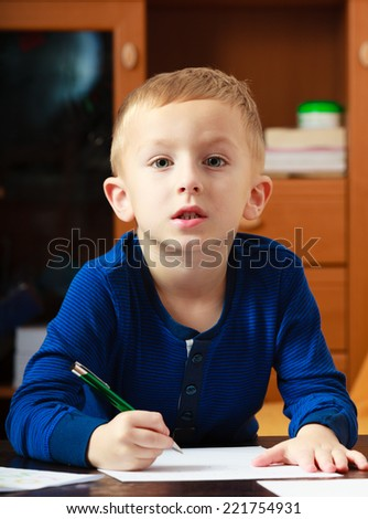 Happy childhood. Blond boy child kid with pen writing on piece of paper doing homework. At home. - stock photo