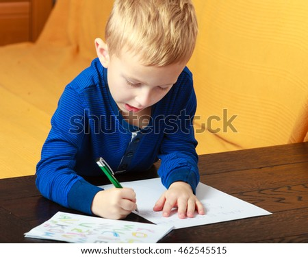 Happy childhood. Blond boy child kid with pen writing on piece of paper doing homework. At home.