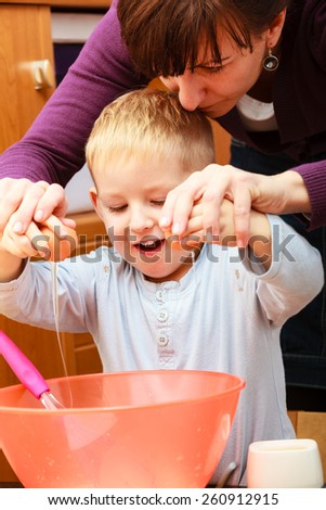 Happy childhood. Boy kid baking preparing cake. Mother young woman teaching showing her son child how breaking egg into bowl. Kitchen. Real. - stock photo