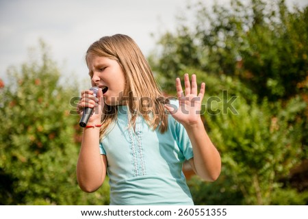 Happy childhood - child singing with microphone outdoor in backyard