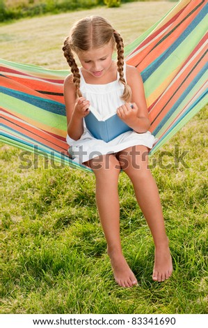 Happy childhood - Cute girl reading a book  in colorful hammock - stock photo