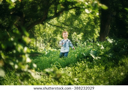 Happy Childhood. Cute Little Boy Having Fun in the Summer Park Outdoors. Cute Blonde Kid in Jeans Clothing. Selective Focus. - stock photo