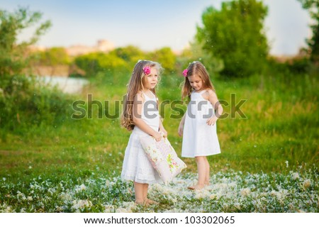 Happy childhood: cute little girls having fun with pillows outdoor