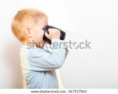 Happy childhood. Funny little boy child kid drinking tea. Indoor - stock photo