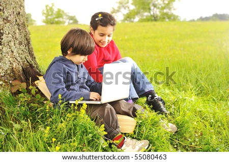 Happy childhood in nature, beautiful scene with laptop under the tree - stock photo