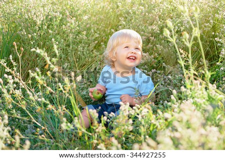 Happy childhood. Little boy with apple plays on a green meadow. - stock photo