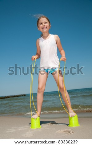 Happy childhood - little girl playing with bucket stilts on the beach - stock photo