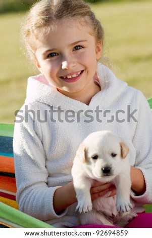 Happy childhood - little girl with cute Labrador puppy in hammock - stock photo