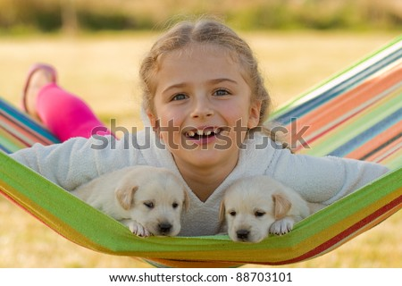 Happy childhood - little girl with cute puppies in hammock - stock photo