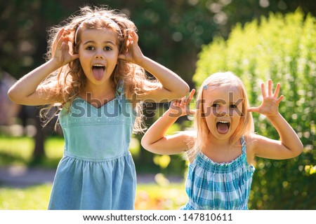 Happy childhood: Little girls having fun together outdoors in park