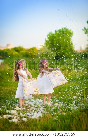 Happy childhood: Little girls having fun with pillows and feathers - stock photo