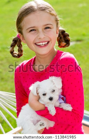 Happy childhood  - lovely girl with cute puppy in the garden - stock photo