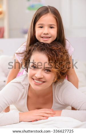 Happy childhood. Pleasant smiling delighted mother and daughter lying on bed and evincing positivity while having fun