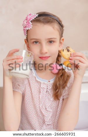 Happy childhood. Portrait of a small girl smiling to the camera while drinking a glass of milk with tasty cookies - stock photo