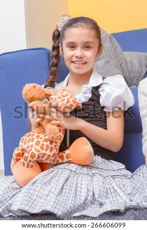 Happy childhood. Small smiling girl holding a toy giraffe and sitting at the couch in children room - stock photo
