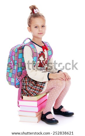 Happy childhood, the family concept.Elegant girl schoolgirl sitting on a stack of books. Isolated on white. - stock photo