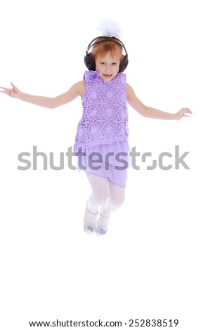 Happy childhood, the family concept.funny little girl jumping while listening to music in big black headphones. Isolated on white. - stock photo