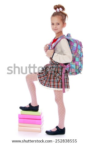 Happy childhood, the family concept.Happy girl schoolgirl holding his foot on a stack of books. Isolated on white. - stock photo